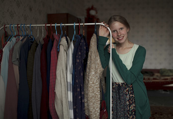 Portrait of pensive Caucasian woman leaning on clothing rack