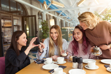 Young beautiful girls taking selfie photo at cafe or coffee shop. Happy women friends having fun, talking together and looking photos at mobile phone. Female friendship, communication concept