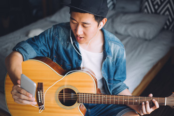 Young Asian man using a mobile phone with headphones while playing guitar in cozy bedroom