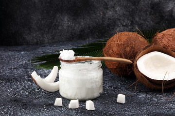 coconut oil and fresh coconuts on grey background.