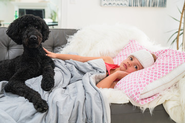 Young girl lying ill on sofa at home with pet dog.