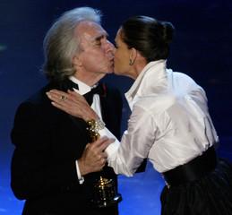 ARTHUR HILLER RECEIVES KISS FROM ACTRESS ALI MCGRAW.