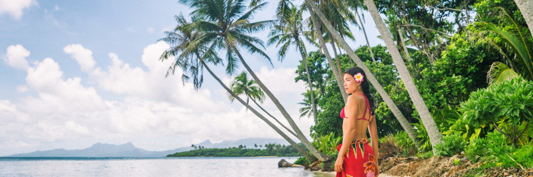 Tahiti luxury exotic travel vacation girl with polynesian flower walking on beach landscape with palm trees. Asian woman in red bikini and beachwear banner panorama.