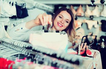 Woman client choosing brassiere in underwear store