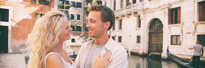 Romantic honeymoon couple in love walking in Venice streets. Lovers tourists in summer Italy travel. Blonde woman and man happy together on Europe vacation holidays. Banner panorama.