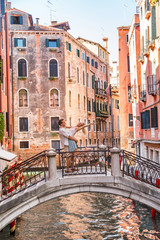 Romantic couple on honeymoon travel in Venice walking on bridge. Lovers romance jumping in love man and woman embracing each other. Europe summer holiday city streets, Italy.