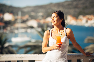 Young female enjoying a colourful cocktail on the panoramic view hotel terrace.Cold delicious cocktail smoothie for the summer hot days.Enjoying summer vacation.Happy female relaxing.Drinking alcohol
