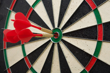 Close up of three darts in bull's eye