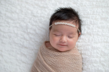 Smiling Baby Girl Wrapped in a Beige Swaddle