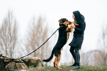 Young active black haired girl in down jacket playing with her lovely dog outdoor. Cheerful happy female have fun and training  puppy with stick. Cute woman dancing with purebred pet. Walk the big dog
