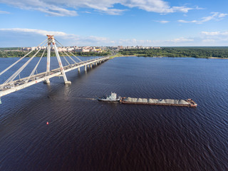 The dry cargo ship barge passes along the Sheksna River after the October cable-stayed bridge. Cherepovets, Vologda region, Russia