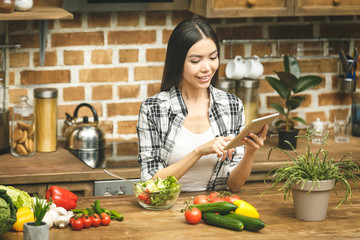 Autocollant pour porte Cuisine Beautiful young woman with tablet computer on kitchen finding recipes and tasting food. Food blogger concept