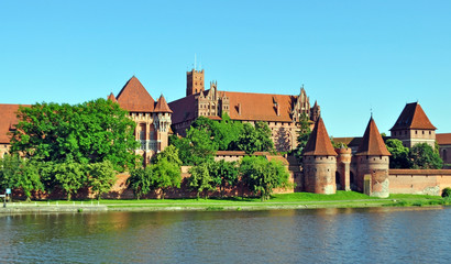 Ancient European knight's castle, which is located in Poland, the city of Malbork. Fortress close-up on the lake surrounded by greenery. tourist center with ancient architecture.