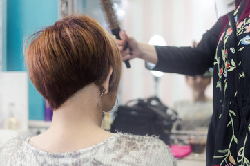hairdresser loves the customer in the salon, woman sits on a chair facing back and imposes a new haircut