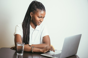 Student woman working with a laptop against a white wall