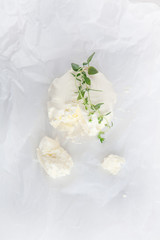 fresh cream cheese wit oregano on white paper and white wood table can be used as background