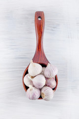 Fresh garlic decorated in a wooden spoon on a white wooden kitchen plate can be used as background