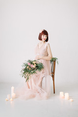 Pregnant girl sits on a decorated chair with large bouquet of flowers with candles in the ground