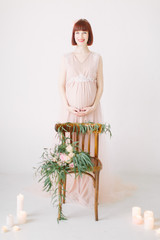 Pregnant girl is standing near decorated chair with large bouquet of flowers with candles in the ground