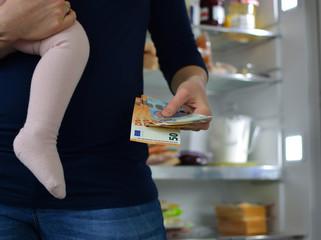 Mutter mit Kind vor Kühlschrank, Konzept für Haushaltskosten