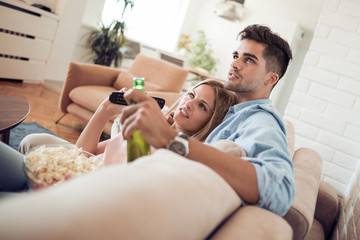 Couple watching TV and eating popcorn.