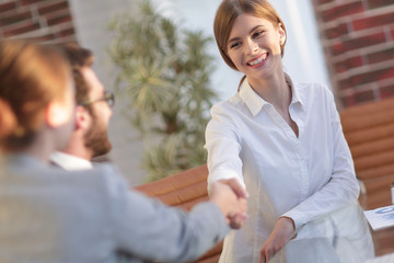 business woman greets the employee with a handshake,