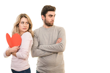 The sad couple stands with a heart symbol on the white background