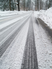 road covered with snow and car tracks