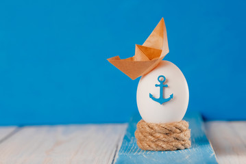 Easter egg with marine decor on a wooden background