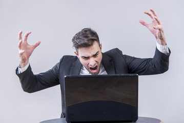 Enraged and furious young business man yelling at his computer