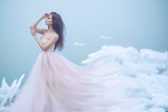 Art portrait of a beautiful young nymph in luxurious strapless ball dress growing into soft clouds. Her eyes closed. Fairytale concept. Copy space