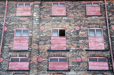 facade of a derelict abandoned old brick industrial building with red painted broken boarded up decaying windows