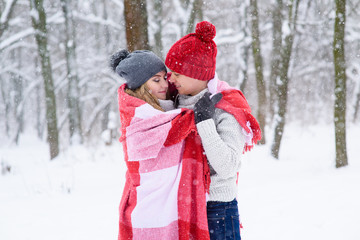Girl and boy make warm each other in winter forest