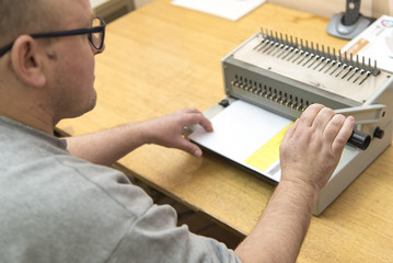Young man using a manual paper binder to bind documents, stack of papers, together