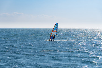 Windsurfing on the sea, backlit view.