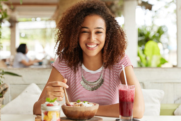Adorabe dark skinned female with Afro hairstyle, wears casual striped t shirt, eats exotic sweet dish, drinks cocktail at outdoor cafeteria, smiles broadly, demonstrates white teeth, rests after work