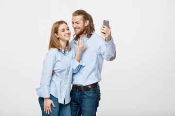 Joyful young loving couple making selfie on camera while standing in white studio background.