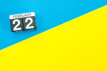 February 22nd. Day 22 of february month, calendar on blue and yellow background flat lay, top view. Winter time. Empty space for text