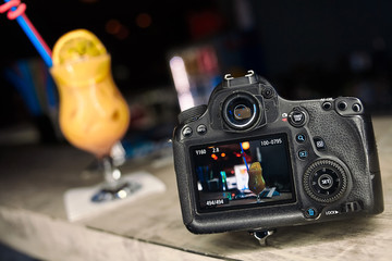 Professional modern DSLR camera low key image. Blurred yellow cocktail on background. Bar counter