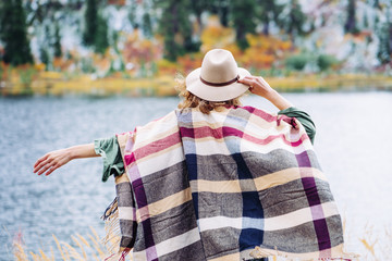 Woman traveling among mountains, enjoy the nature. Forest and lake wearing hat and poncho, boho and wanderlust style
