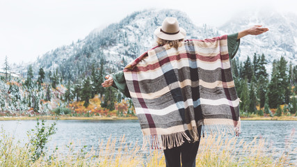 Adventure woman feeling happy among mountains, enjoy the nature landsape. Forest and lake, wearing hat and poncho, boho and wanderlust style