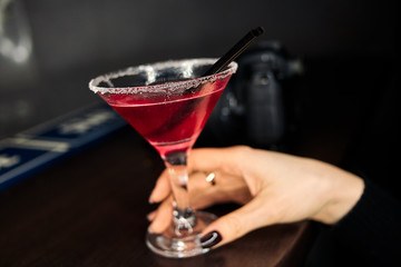 A glass of a cosmopolitan in woman`s hand. Pink alcoholic cocktail.  Blurred photo camera on dark background