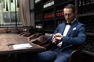 handsome man in stylish suit looking at watch while waiting for date at restaurant