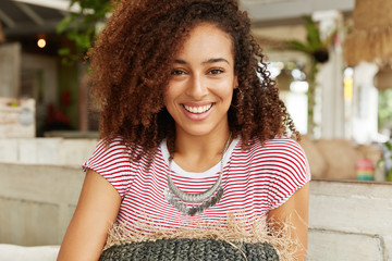 Close up of attractive curly African woman with dark healthy skin, has broad smile while spends free time at coffee shop with friends, meet to celebrate successfully passed exams at university