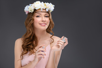 beautiful young woman in floral wreath spraying perfume isolated on grey
