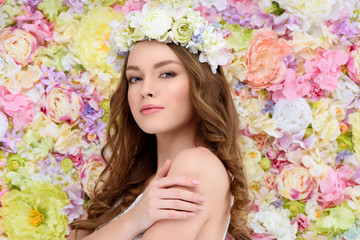 sensual young woman in floral wreath on flral background