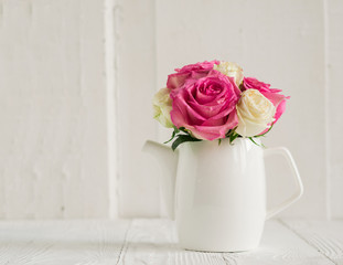 Bouquet of fresh pink roses in a white jug on a table on a white background. Wooden vintage background. Minimalism.