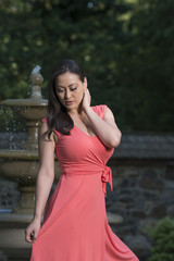 Stunning biracial (Asian and Caucasian) woman poses in garden in pink sun dress with fountain behind her