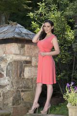 Stunning biracial (Asian and Caucasian) woman poses in garden in pink sun dress