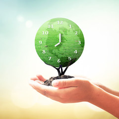 World environment day concept: Human hands holding clock of global grass tree on blurred nature background